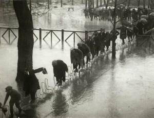 Žmonės mėgina kėdėmis pereiti Mezon Lafito hipodromą Senos potvynio metu. Paryžius. 1924