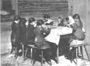 Vaikai dirbtuvėje peiliais apdrožia gintaro gabaliukus. Palanga. Apie XIX a. pab.–XX a. pr.
