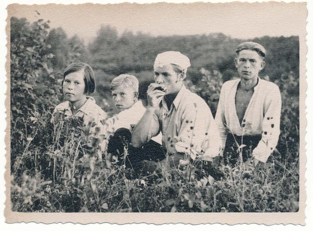 Alfonsas Nyka-Niliūnas (groja lūpine armonikėle) su seserimi Ona ir broliais Stasiu (kairėje) bei Adolfu (dešinėje). Apie 1938 metus Nemeikščiuose. Maironio lietuvių literatūros muziejaus archyvo nuotrauka