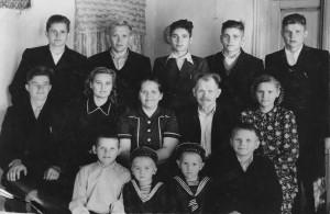 Pyragų šeima. Pirmoje eilėje sėdi pirmas iš dešinės Vytautas Pyragas. Aleksandrovskojės kaimas, Tomsko sritis, Rusija. 1956