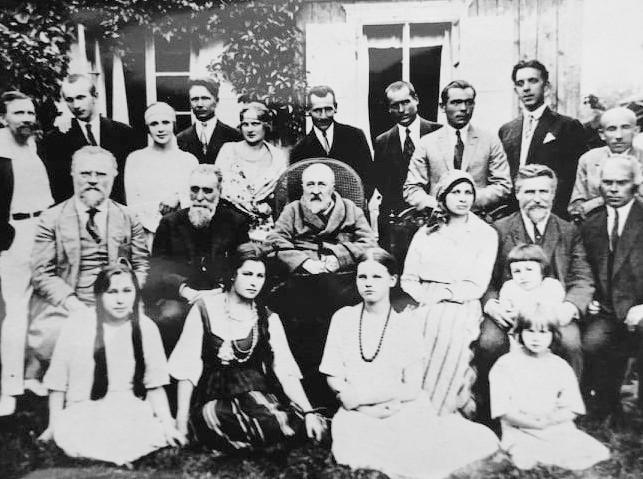 """Palangoje prie Vaineikių namų, minint pirmo viešo lietuviško spektaklio """"Amerika pirtyje"""" 25 metų sukaktį. Sėdi (iš kairės): J. Šliūpas, J. Basanavičius, J. Jablonskis, S. Vaineikienė, L. Vaineikis su sūnumi Jurgiu, nežinomas vyras; stovi (iš kairės): L. Gira, A. Kupstas,  T. Vaičiūnienė, P. Čiurlionis, nežinoma moteris, nežinomas vyras,  K. Glinskis, P. Kubertavičius, S. Pilka, M. Untulis. Sėdi ant žemės  L. ir E. Vaineikytės ir kiti. 1924"""