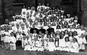 Anykščių vaikai su vikaru Vincentu Arlausku (centre kairėje) ir klebonu Jurgiu Žitkevičiumi (centre dešinėje) po Pirmosios Komunijos prie šoninių bažnyčios durų 1956-aisiais